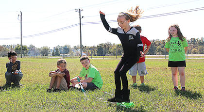 Elizabeth Morris jumps and sets her rocket into motion during 4-H Science Day. Other students pictured include Goto Masaharu, Aiden Bickett, Carson Osborne, Owen Daugherty and Jenna Mullins.