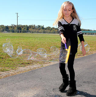 Elizabeth Morris creates a strand of bubbles.