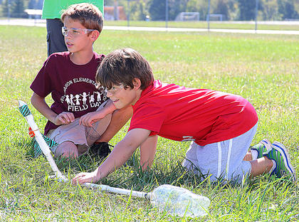 Owen Daugherty aims his rocket toward the target as his partner, Aiden Bickett, assists.