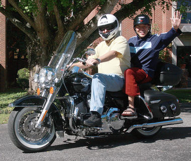 Tenpa Phuntsok waves from the back of Jay Batt's motorcycle as they leave the Loretto Motherhouse on Saturday.