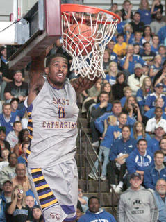 St. Catharine Junior forward DeShawn Mitchell scores one of the many dunks during the game.