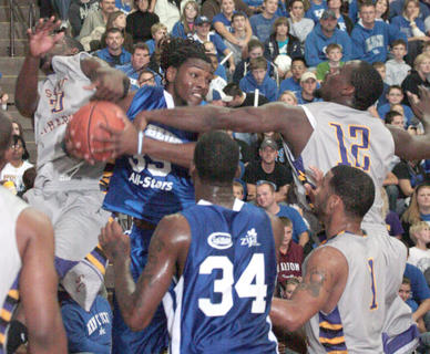 Former Morehead State star Kenneth Faried, now of the Denver Nuggets, grabs a rebound in between a pair of Patriots.