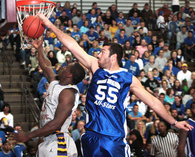 Josh Harrellson of the New York Knicks blocks a shot by St. Catharine senior forward Kashiff Carr during an exhibition game between the Big Blue All-Stars and the St. Catharine College Patriots Oct. 20 at Marion County High School. The Big Blue All-Stars won the game 126-116 in front of a packed Roby Dome crowd. 