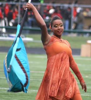 Jarie Newby spins and twirls her flag around her head.