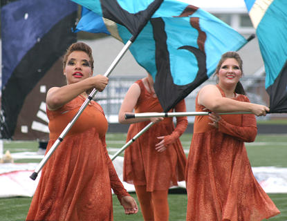 Megan Newton, left, and Katie Elmore wave their flags in time to the music.
