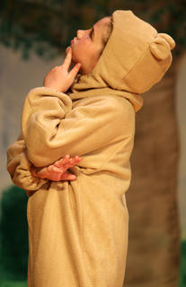Winnie the Pooh, played by Mya Kehm, tries to come up with a plan to retrieve honey out of a tree.