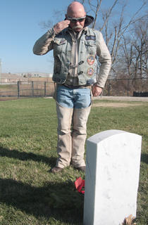 Joe Robinson of the Patriot Guard Riders of Kentucky offers a salute after placing a wreath.