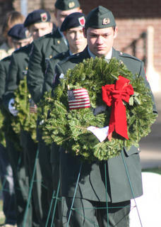 Andrew Villanueva carries a ceremonial wreath in honor of the Army.