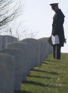 A member of the Marion County Veterans Honor Guard searches for a gravesite to place his wreath.