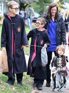 Brothers Ethan Thompson, 11, and Bryce Thompson, 9, both dressed as Harry Potter for Halloween while their little brother, Knox, who will be two years old on Saturday, dressed as a skeleton. Also pictured is their mother, Robyn Thompson.