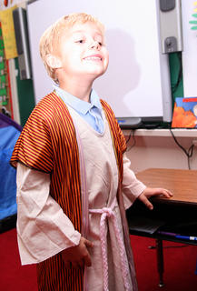 Gabriel Mullins, who dressed as St. Gabriel, smiles big to pose for a picture.