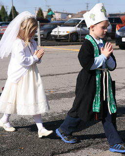Brinton Bland, as St. Patrick, and Abigail Caldwell, as St. Therese the Little Flower, walk to church for an All Saints Day Mass.
