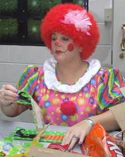 The staff of the Marion County Public Library got in the Halloween spirit by dressing up for the holiday. Young adult librarian Elaine Rahn clowns around while putting together goodie bags.