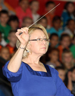 Joni Farmer, the band director at St. Charles Middle and Lebanon Middle schools, instructs the band during their performance.