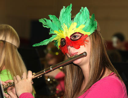 A masked Paige Thomas plays the flute.