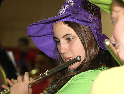Maria Ferriell wears a witch hat while playing the flute.