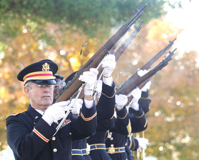 Casings fly through the air as the Marion County Honor Guard fires a three-round volley.