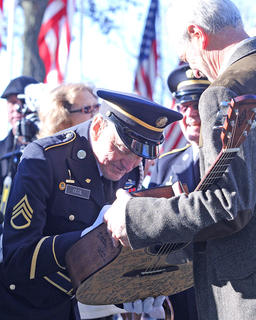 Joseph Cecil, a World War II veteran, signs Terry Wooley's guitar, a guitar that has been signed by many veterans before him.