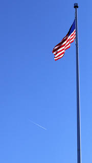 A plane streaks by as the flag waves proudly at the Lebanon National Cemetery.