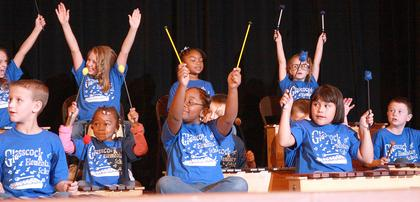Glasscock Elementary students throw their hands up at the end of a song.