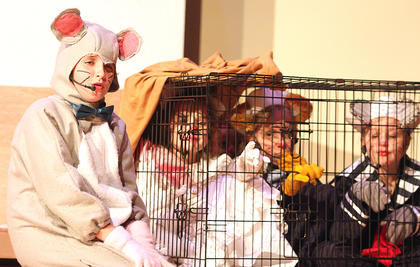 Savannah Chapman plays the part of Roquefort, a mouse and also a friend of the cats, who attempts to save the cats after they have been catnapped. Pictured trapped in the cage are Abigail Adams (as Marie), Gracie Wilson (as Toulouse) and Chloe Allen (as Berlioz).