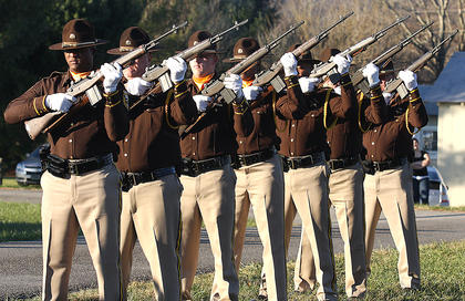 The Jefferson County Sheriff&#039;s Honor Guard fires a three-round volley at Old Liberty Cemetery during the graveside service.