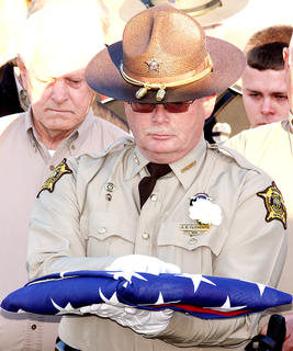 Sheriff Jimmy Clements prepares to present a flag to Rakes family in his honor.