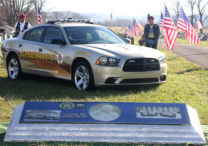 Deputy Anthony Rakes Dodge Charger sits near his gravesite, along with the top of his casket, which was illustrated with photos of him with Sheriff Jimmy Clements and the other members of the sheriffs office.