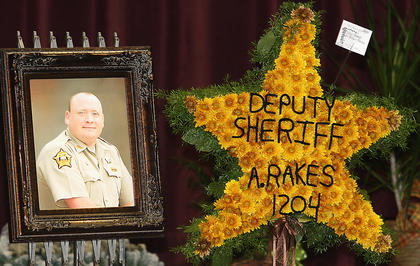 A photo of Deputy Anthony Rakes and a flower arrangement in the shape of a sheriff's badge adorned his casket during his funeral service Saturday afternoon at Marion County High School.