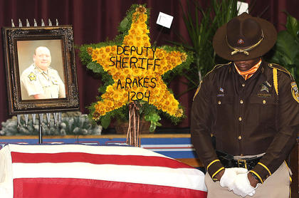 A Jefferson County Sheriff&#039;s Department Honor Guard member stands guard to watch over Rakes&#039; casket prior to his funeral Saturday at Marion County High School.