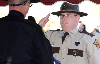 Adam Rainwater of the Green County Sheriffs Department salutes Lebanon Police Officer Greg Young after they both worked together to fold the flag that was draped on Rakes&#039; casket and presented to Rakes&#039; family.