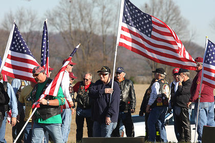 Members of the Patriot Guard Riders place flags throughout the Old Liberty Cemetery in honor of Deputy Rakes.