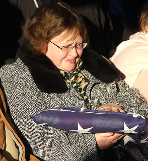 Anita Elder, Rakes sister, holds a flag that was presented to her during the graveside service.