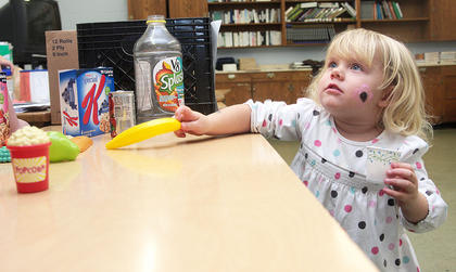 Kylee Hickey reaches for a plastic banana. Students were asked to choose a food that they like from the options on the table.