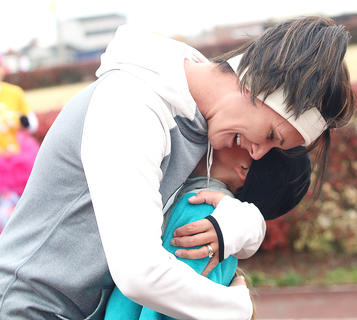 Sarah Thomas gives her daughter, McKenna Thomas, a big hug after they complete the practice 5k together. McKenna Thomas is a Girls on the Run participant at West Marion Elementary School.