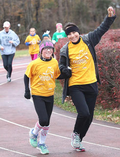 Katie George holds Maggie Jo Benningfield's hand and holds her other hand up to the sky in celebration as they make their way around the track. Benningfield is a fifth grade student at St. Augustine Grade School and George is a Girls on the Run coach at St. A.