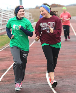 Emily Tungate, left, and Tina Hernandez, both students at St. Charles Middle School, share a laugh as they run together.