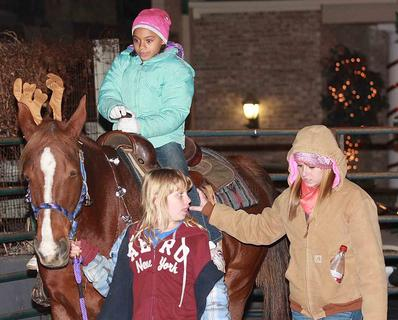 Paige Spalding gets a ride from Shady as Catherine Brak and Morgan Goodlett of the Washington County 4-H Young Riders guide the horse around the ring.