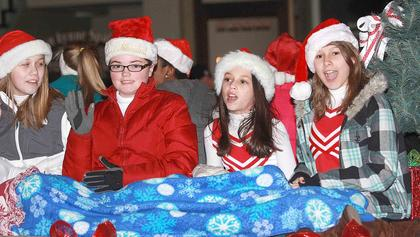 From left, Kaylee Thomas, Paige Mattingly, Kelly Miles, and Haley Ruley go for a ride on the St. Augustine cheerleaders' float.