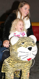 Annslee Wooldridge squeals in delight as she rides one of the animated stuffed animal rides during Dickens Christmas Friday evening. Riding with her is Brittany Myers.