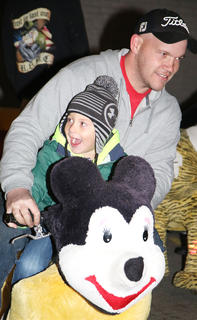 Keegan Gribbins and his dad, Matthew, ride one of the animated stuffed animal rides during Dickens Christmas Friday evening.
