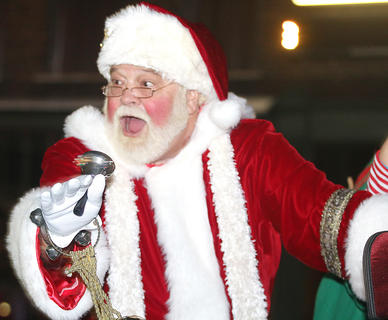 Santa Claus interacts with the crowd during the Dickens Christmas Parade Friday evening.