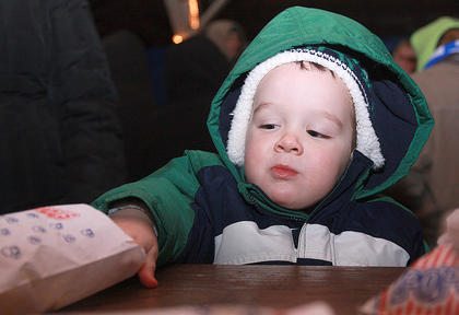 Tanner Reed, 2, reaches for some more popcorn during Christmas at the Park.