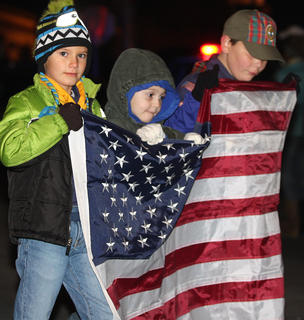 Connor Zink, William Buckman and Carter Ballard hold an American flag while walking in the parade with Cub Scout Pack 90.