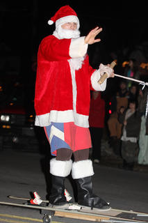 Eric Miles, dressed as a skiing Santa, carefully waves to the crowd.