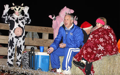 Donnie Miles, owner of Loretto Foodland, passes out candy to the crowd as his wife, Pam, stays warm underneath a blanket beside him.