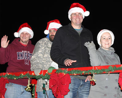 Nicole Hughes Smith, her husband Derek Smith, his brother Patrick Smith and Patrick Blandford all wave to the crowd from atop the Loretto Lumber float.