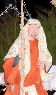 Tyler Jones, dressed as a shepherd, walks along a float featuring the nativity scene.
