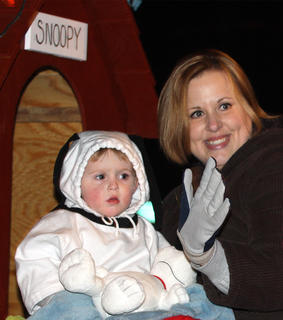 Jill Despain waves to the crowd as her son Gavin, dressed as Snoopy, surveys the mass of people for a familiar face.