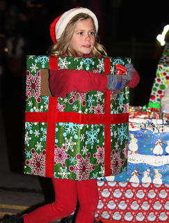 Shelby Edlin, dressed as a giant present, helps pass out candy during the parade.